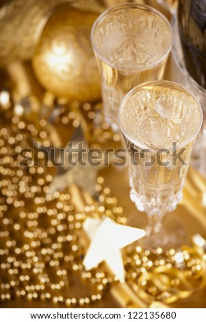 champagne in ice bucket against festive gold background