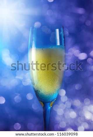 champagne in wineglass on a blue background.