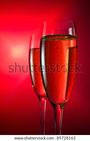 champagne in wineglass on a red background.