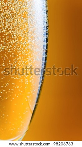 champagne in wineglass on a yellow background.