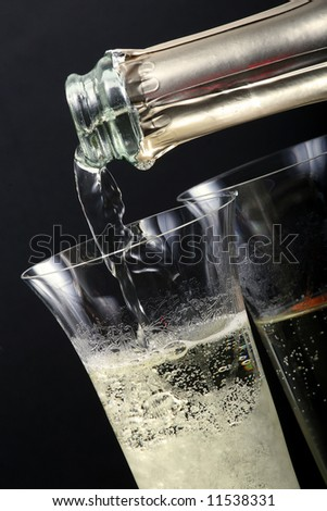 Champagne poured in to the glass on the black background