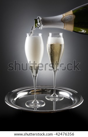 Champagne pours from bottle into two crystal flutes placed on silver tray