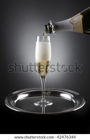 Champagne pours into flute which sit on a silver tray