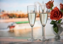 Champagne. Sparkling wine in glasses and a bouquet of roses in a white vase against the background of a window overlooking the river