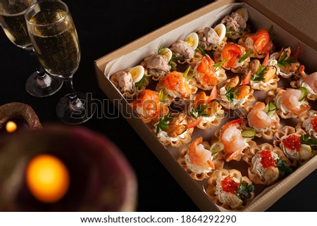 Champagne, tartlets, seafood salads. Cardboard box with food with home delivery. Gift for holiday, party, family dinner. Catering. Delicious snacks.