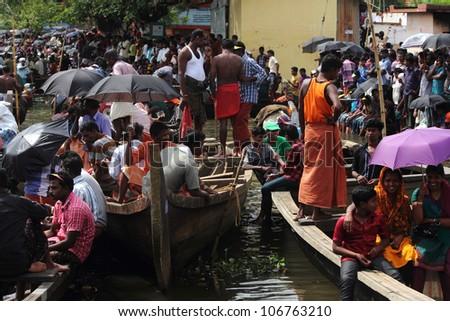 CHAMPAKKULAM, INDIA - JUL 03 : People in groups gathered to watch the Snake boat racing at the banks of Pumba river on July 03, 2012 at Champakkulam, Kerala, India.