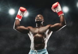 Champion. African boxer raising his arms in winner gesture, stadium lights background