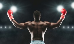 Champion. African boxer raising his arms in winner gesture, stadium lights background, back view