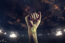 Champion. Award of victory, male hands tightening the golden medal of winners against cloudy dark sky. Sport, competition, championship, winning, achieving the goal. Prize for success and honor.