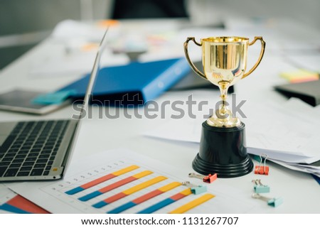 champion golden trophy on table.Award trophy on working table with document and contract #1131267707
