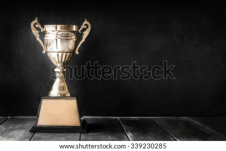 champion golden trophy on wood table with blackboard copy space