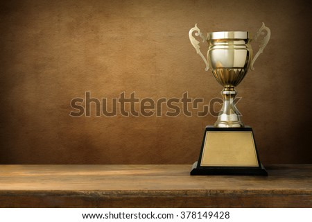 champion golden trophy on wood table with copy space