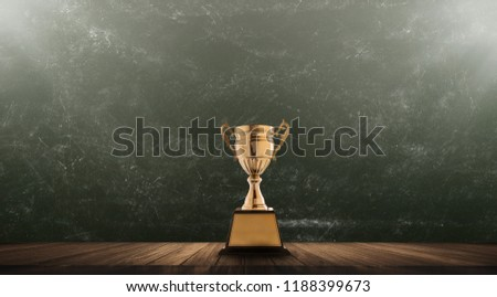 champion golden trophy placed on wooden table with blackboard background copy space ready for your design win concept. #1188399673