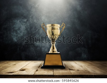 champion golden trophy placed on wooden table with dark background copy space ready for your design win concept. #595845626
