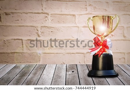 champion golden trophy with lens flare effect on wooden table and old vintage brick wall background, winner, success and congratulation concept, copy space for display of product presentation