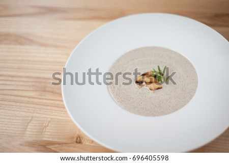 Shutterstock Champion mushrooms cream soup in white plate on wooden background