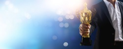 champion of the best and achievement, winner or victory concept, celebration to successful businessman celebrate in success business holding golden award on soft blue background with bokeh