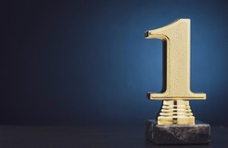 Champion or Winner gold trophy in the shape of a textured 3D number one for 1st place over blue with copy space