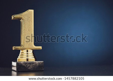 Champion or Winner gold trophy in the shape of a textured 3D number one for 1st place over blue with copy space Сток-фото ©