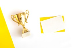 Champion trophy cup, envelope and blank sheet for text on a geometric white and yellow background. Winning concept. Top view. Flat lay. Sports layout and tabletop mockup with copy space.