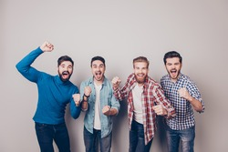 Champions! Four amazed young men are standing and gesturing for the victory on pure background in casual outfit and jeans. They are fans of sports games as football, basketball, hockey, baseball