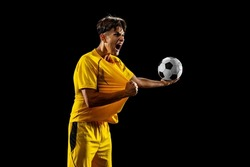 Championship winning game. Happy proud male football player in yellow uniform isolated over dark background. Successful competition. Concept of action, speed, energy, sport, competition and ad.