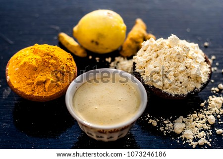 Chana,haldi,limbo ka ubtan or ayurvedic face pack of Turmeric, Lemon, and gram flour on wooden surface for good skin and no acnes or pimples.