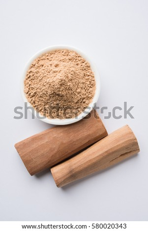Chandan or sandalwood powder with stocks and traditional mortar, Isolated over clear colourful background. Selective focus