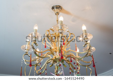 Chandelier Lamp beautiful luxury expensive chandelier hanging under ceiling . The lamp in the beautiful room .Brass chandelier with crystal. Chandelier ceiling lights