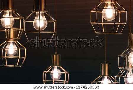 Chandelier with hanging bulb lamps, yellow LED lighting elements covered with metal wire frame lampshades, photo with selective focus - Shutterstock ID 1174250533