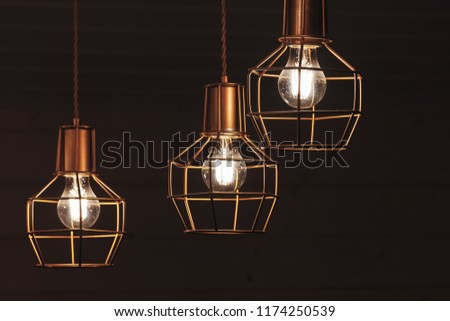 Chandelier with hanging three bulb lamps, yellow LED lighting elements covered with metal wire frame lampshades, photo with selective focus #1174250539