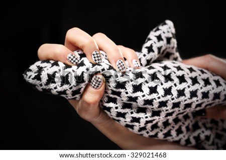 Chanel grille, black and white pattern on your nails. Woman\'s hand with fingernails painted in black and white checkered