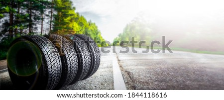 Change a car seasonal tire summer forest road with trees background. Change for winter tire. Banner Selling off. Or Background automechanic
