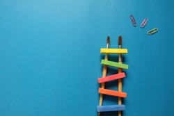 Change Concepts ,Concepts to add color to life , Change Concepts ,Time Concept,  fun,  - Colorful ladder made of chalk with paintbrush ,Paperclip .Blue background.
