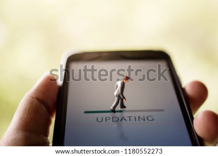 Change for New Challenge in Life or Upgrade Technology Concept. Miniature Fugure of Businessman Walking with Update Progressive Bar on Smartphone Screen  #1180552273