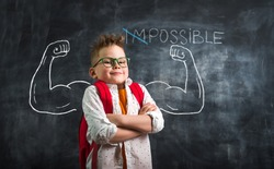 Change impossible on possible. Funny kid with strong arms against blackboard