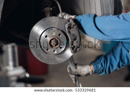 change the old drive to the Brand new brake disc on car in a garage. Auto mechanic repairing . #533329681