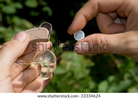 Changing a digital hearing aid battery.