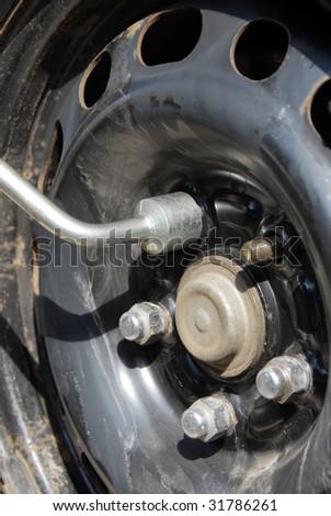 changing a winter tire, bolt unscrewing closeup