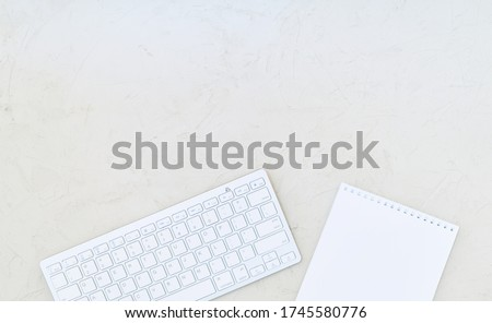 Changing table, white wireless keyboard and notebook with blank sheet on a wooden surface. Copy space ストックフォト ©