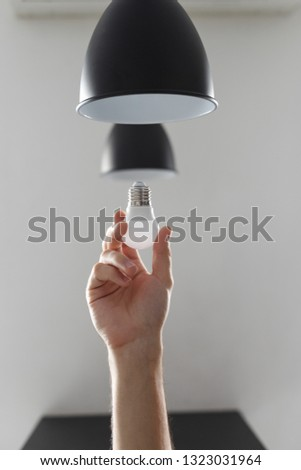 Changing the bulb for led bulb in floor lamp in black colour. On light gray background. #1323031964