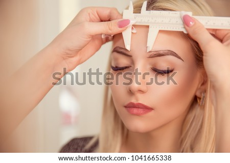 Changing the shape of the brows. Stylist measuring the eyebrows with the ruler. Micropigmentation work flow in a beauty salon. Woman having her eye brows tinted with Semi-permanent makeup.