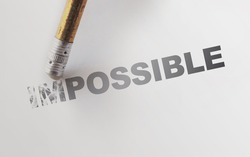 Changing the word impossible to possible with a pencil eraser. Motivation startup concept.