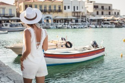 Chania travel vacation woman on famous travel destination. Young fashion tourist girl in hat walking at bay. Summer wanderlust. Crete, Greece