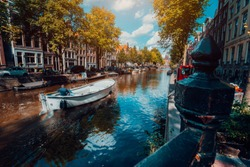 Channel in Amsterdam in autumn sunlight. Boat floating tree-lined canal, vibrant reflections, white clouds in the sky. Netherlands houses landmark landscape
