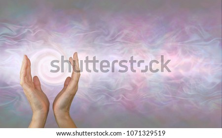 Channeling Vortex healing energy  - female hands held parallel with a white spiralling vortex energy formation and pale pink blue grey misty ethereal energy field background with copy space