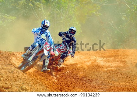 CHANTABURI, THAILAND - NOV 20: A pair of unidentified riders participate in the final round of the 2011 Thailand motocross championship on November 20, 2011 in Chantaburi, Thailand.