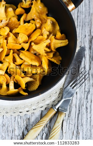 Chanterelle mushrooms on the frying pan with fork and knife