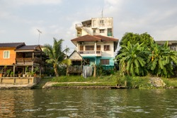 Chao Phraya houses and boats on the riverside during sunset hours taken from the boat ride. Ayutthaya, Thailand