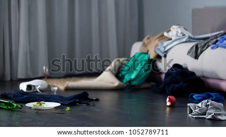 Chaos and mess in room after party, cloth and food on floor, bachelor apartment